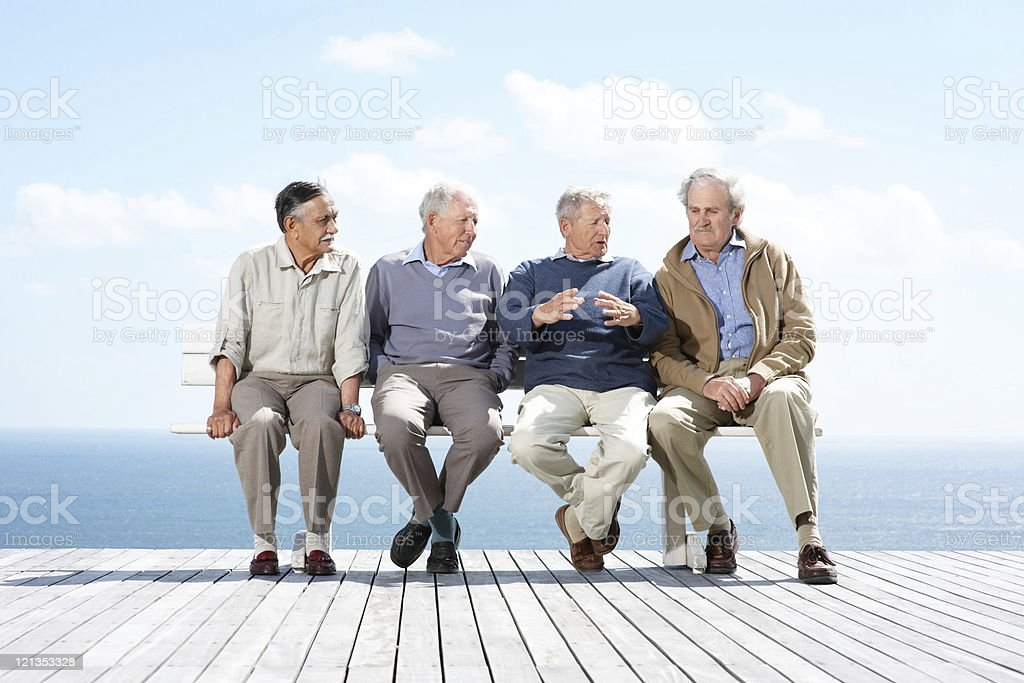 Group of mature male friends sitting together on bench royalty-free stock photo