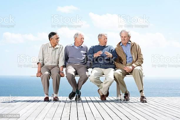 Gruppe Von Reife Männliche Freunde Zusammen Auf Einer Bank Sitzend Stockfoto und mehr Bilder von Abmachung