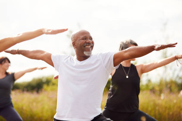 Group Of Mature Men And Women In Class At Outdoor Yoga Retreat Group Of Mature Men And Women In Class At Outdoor Yoga Retreat wellbeing stock pictures, royalty-free photos & images