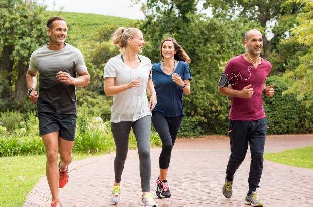 group of mature people jogging - jogging stock pictures, royalty-free photos & images