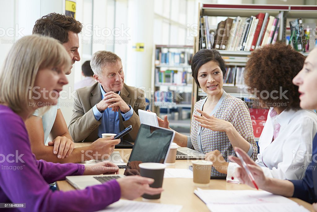 Group Of Mature Students Collaborating On Project In Library royalty-free stock photo