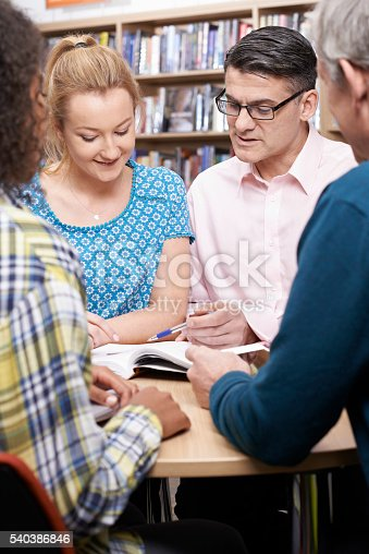 877026364 istock photo Group Of Mature Students Studying In Library 540386846