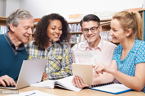 877026364 istock photo Group Of Mature Students Studying In Library 646981924