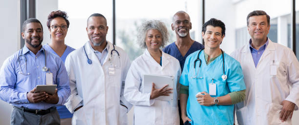 Group of medical professionals smile together for a photo stock photo