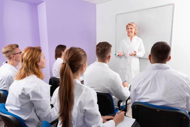 gruppe von medizinstudenten aufmerksam zuhören, um der lehrerin im klassenzimmer vortrag - lautsprecher test stock-fotos und bilder
