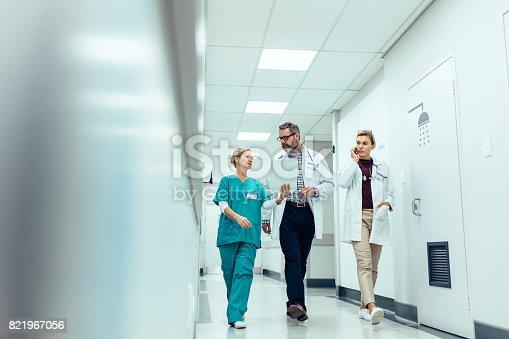 istock Group of medics discussing along hospital corridor 821967056