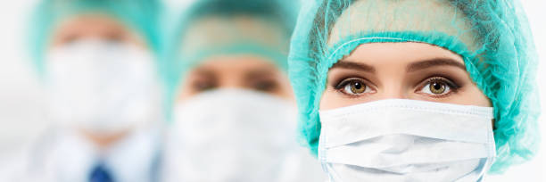 Group of medics Three doctors faces wearing protective mask and green surgeon's cap in row closeup. Surgeon's eyes close up gazing intently in camera. Letterbox view letterbox format stock pictures, royalty-free photos & images