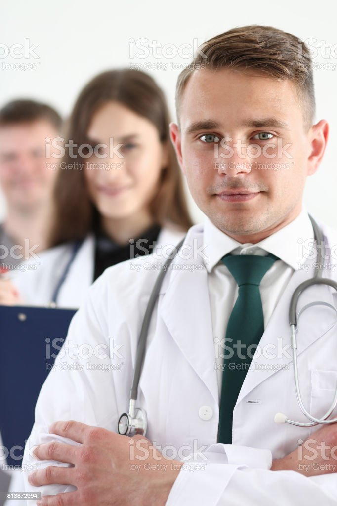 Group of medics proudly posing in row and looking in camera stock photo