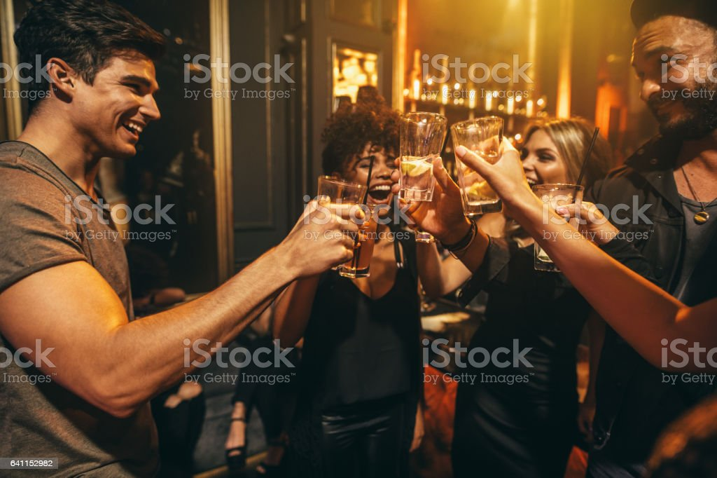 Group of men and women enjoying drinks at nightclub stock photo