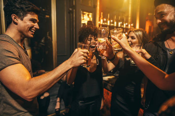 group of men and women enjoying drinks at nightclub - happy hour stock photos and pictures