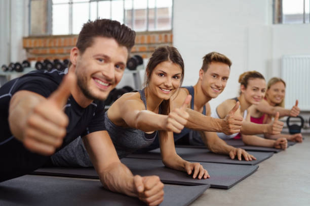 Group of men and women give the camera a thumbs up stock photo