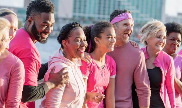 pembe erkek ve kadın grubu, meme kanseri rallisinde - breast cancer awareness stok fotoğraflar ve resimler