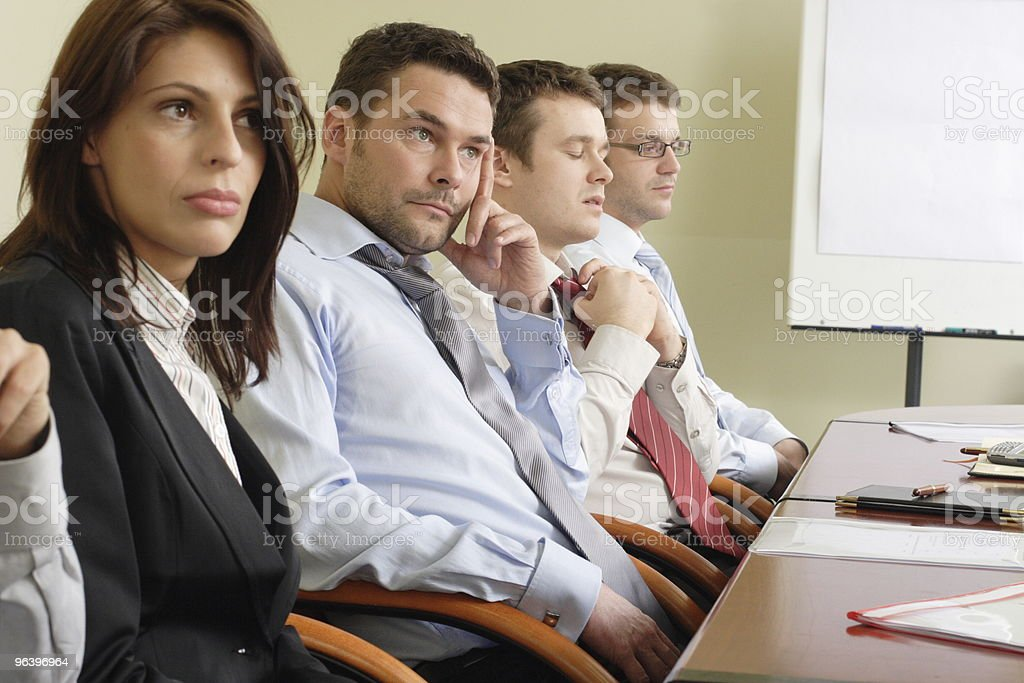 Group of men and women sitting at a desk looking bored stock photo