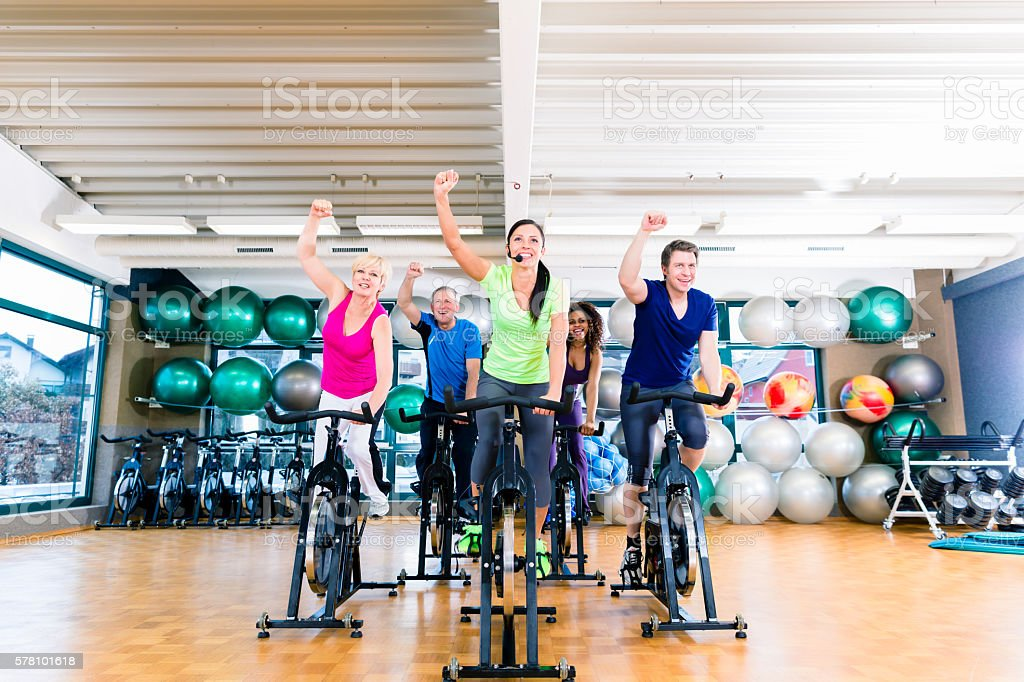 Group of men and women spinning on fitness bikes stock photo