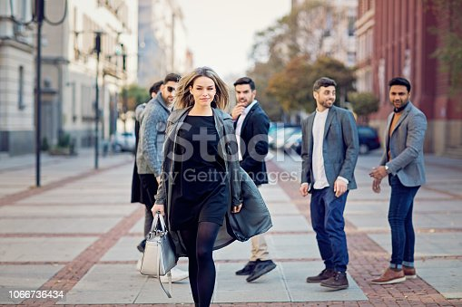 Group of men are looking back and flirting with a beautiful woman