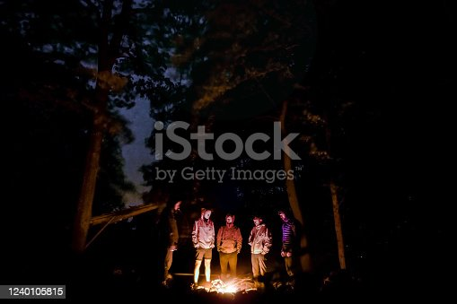 istock Group of men, backpackers, tourist standing around campfire in forest under oak trees and sky is visible between trees White Carpathians in Czechia (Carpathian mountain range) 1240105815