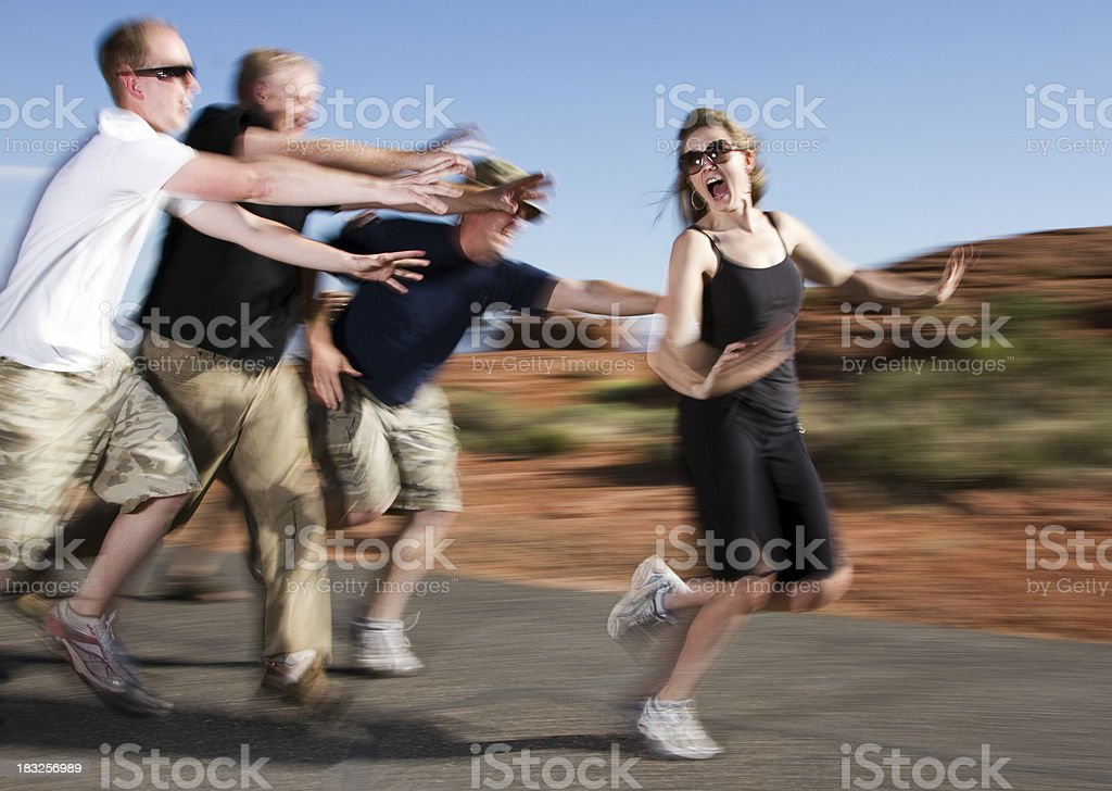 Group of Men Chasing a Woman stock photo