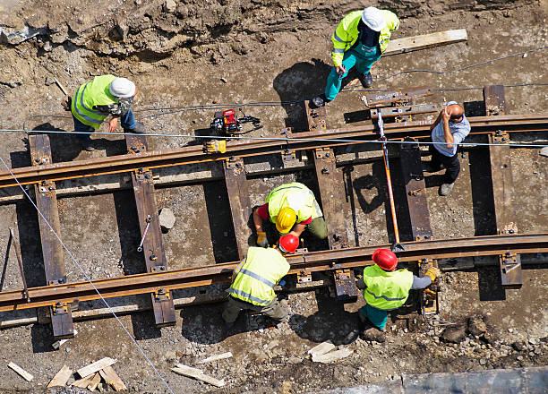 A group of men constructing a railway construction workers are building a new railway line tramway stock pictures, royalty-free photos & images