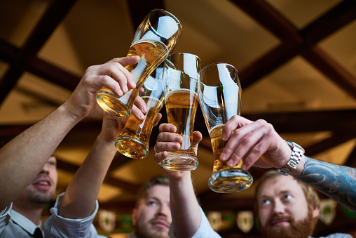 Handsome young men clinking full beer glasses while celebrating Friday at night in bar