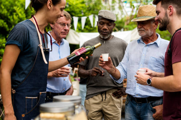 group of men drinking local red wine together - traditional festival stock photos and pictures