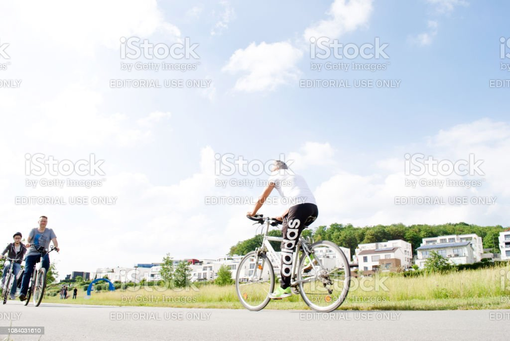 Group of men enjoying the summer day biking around the lake in Phoenix See, Dortmund - Germany. Luxury apartments at the background stock photo