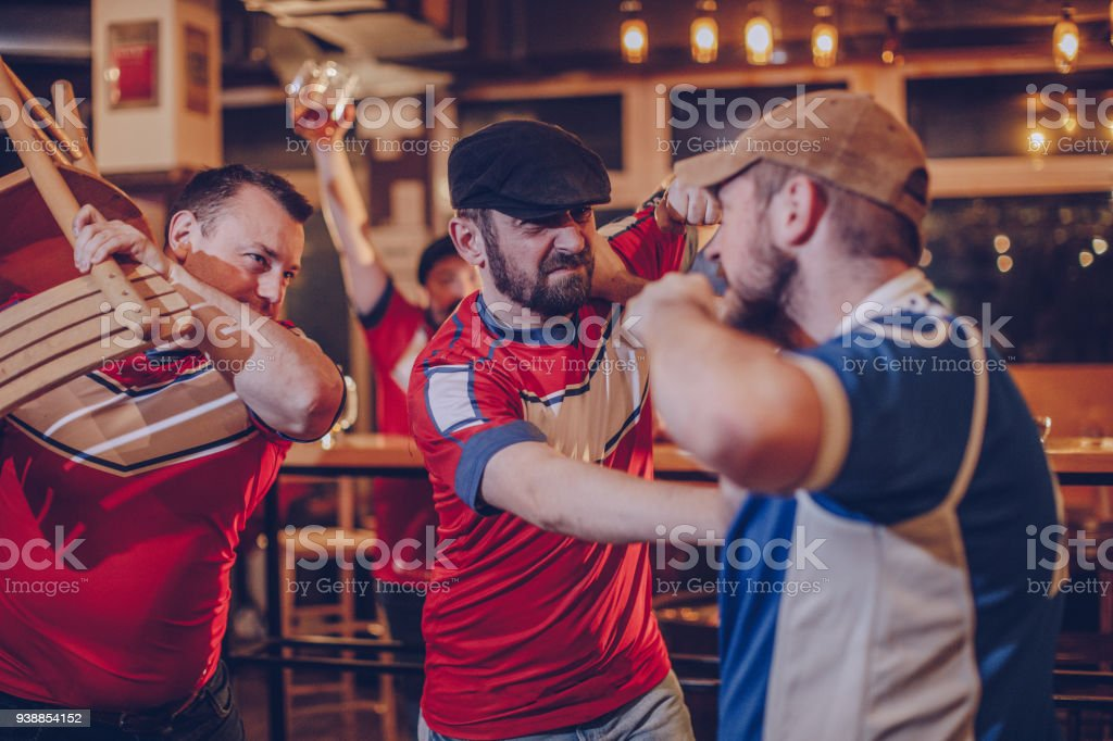 Group of men fighting in bar stock photo