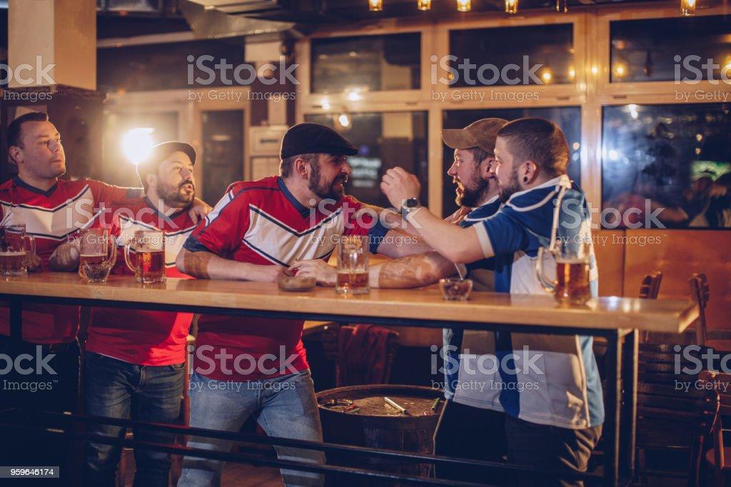 Grupo de hombres que luchan en la barra - Foto de stock de Aclamar libre de derechos