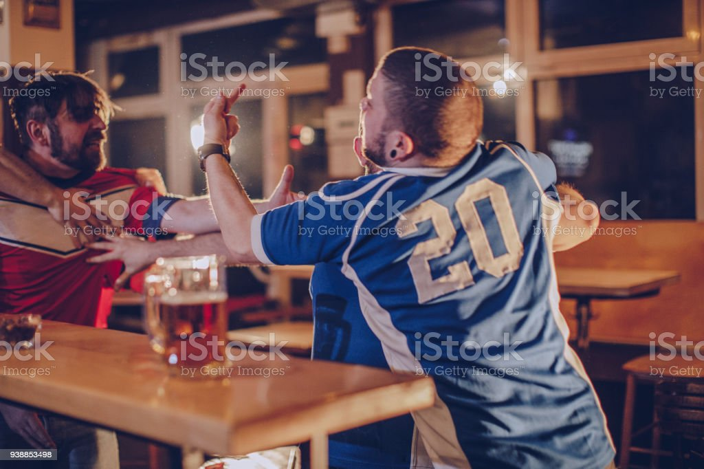 Group of men fighting in sports bar stock photo