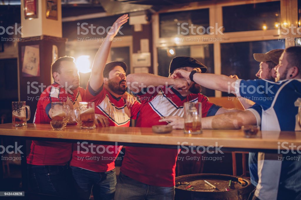 Group of men fighting in sports pub stock photo