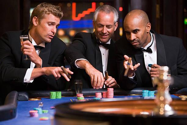 group of men gambling at roulette table - guy with cigar stockfoto's en -beelden