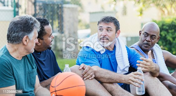 A group of four multi-ethnic mature and senior men in their 40s, 50s and 60s, taking a break after playing basketball. They are sitting on an outdoor court with water bottles and towels, relaxing, and talking.