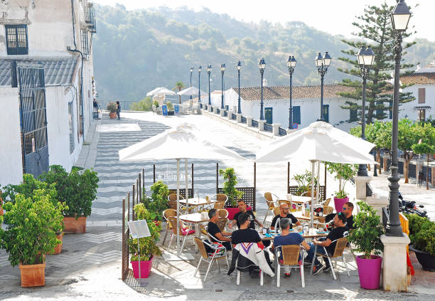 Group of men having a drink at a terrace in the center of Frigiliana stock photo