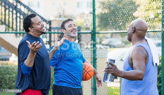 A group of three mature multi-ethnic men hanging out together, playing basketball outdoors.