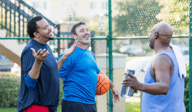 Group of men having fun on basketball court A group of three mature multi-ethnic men hanging out together, playing basketball outdoors. only mature men stock pictures, royalty-free photos & images