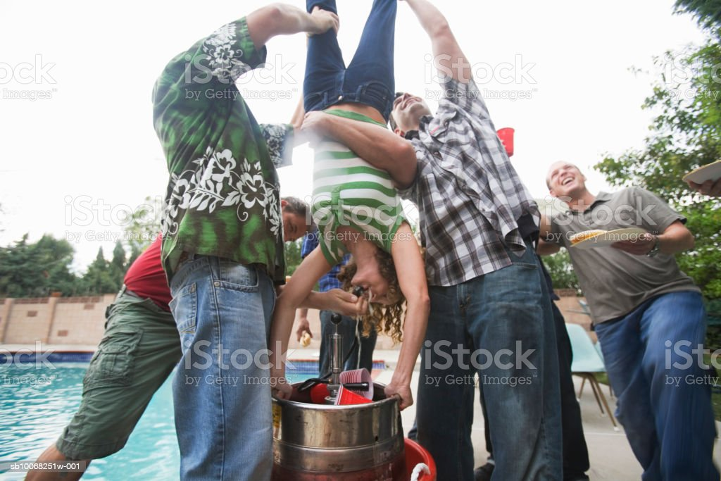 Group of men holding woman upside-down to do 'keg stand' royalty-free stock photo