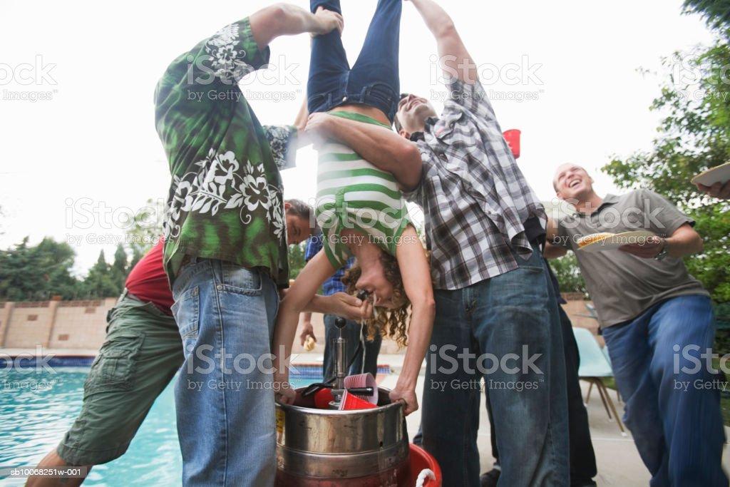Mujer con grupo de hombres sosteniendo cabeza abajo para hacer'keg stand' foto de stock libre de derechos