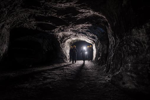 Group of men in a dark mine underground - mining concepts