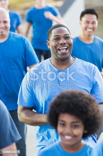 istock Group of men in blue running together, community event 538800378