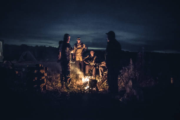 Group of men people travelers tourist resting camp fire in outdoors camp after long hunting day in the night Group of men people travelers tourist resting campfire in outdoors camp after long hunting day in the night hunter stock pictures, royalty-free photos & images