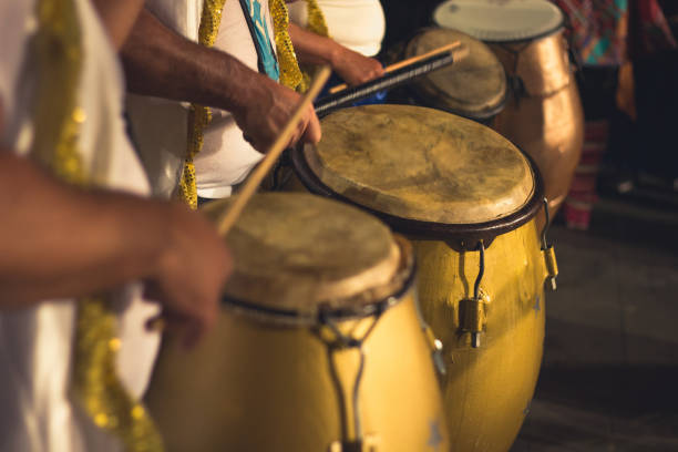 Group of men playing yellow drums at carnival parade at night stock photo