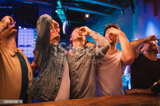 Group of male friends taking shots together on their night out.