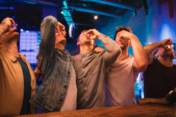 Group of Men Taking shots Group of male friends taking shots together on their night out. tequila shot stock pictures, royalty-free photos & images