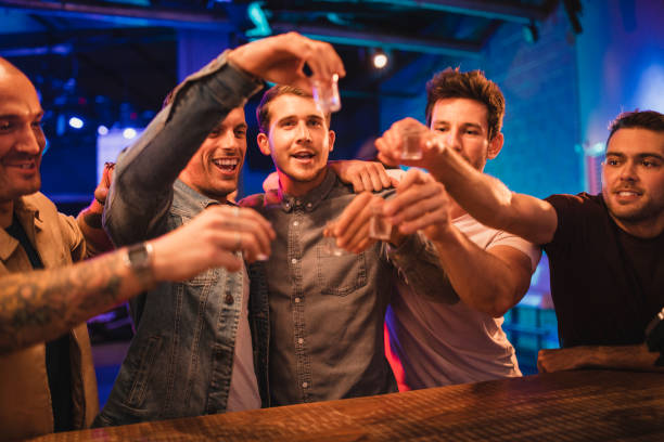 Group of Men Toasting Their Drinks Group of men on a night out toasting their shots before drinking them all in one go. They're celebrating the new year of 2019. tequila shot stock pictures, royalty-free photos & images