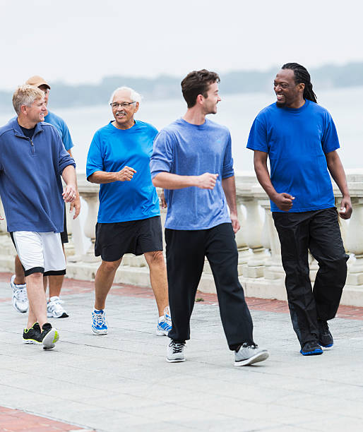Group of men walking and talking stock photo