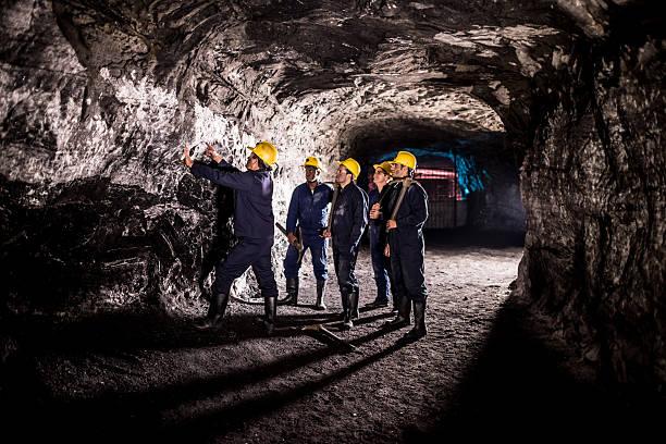 group of men working at a mine - unterirdisch stock-fotos und bilder