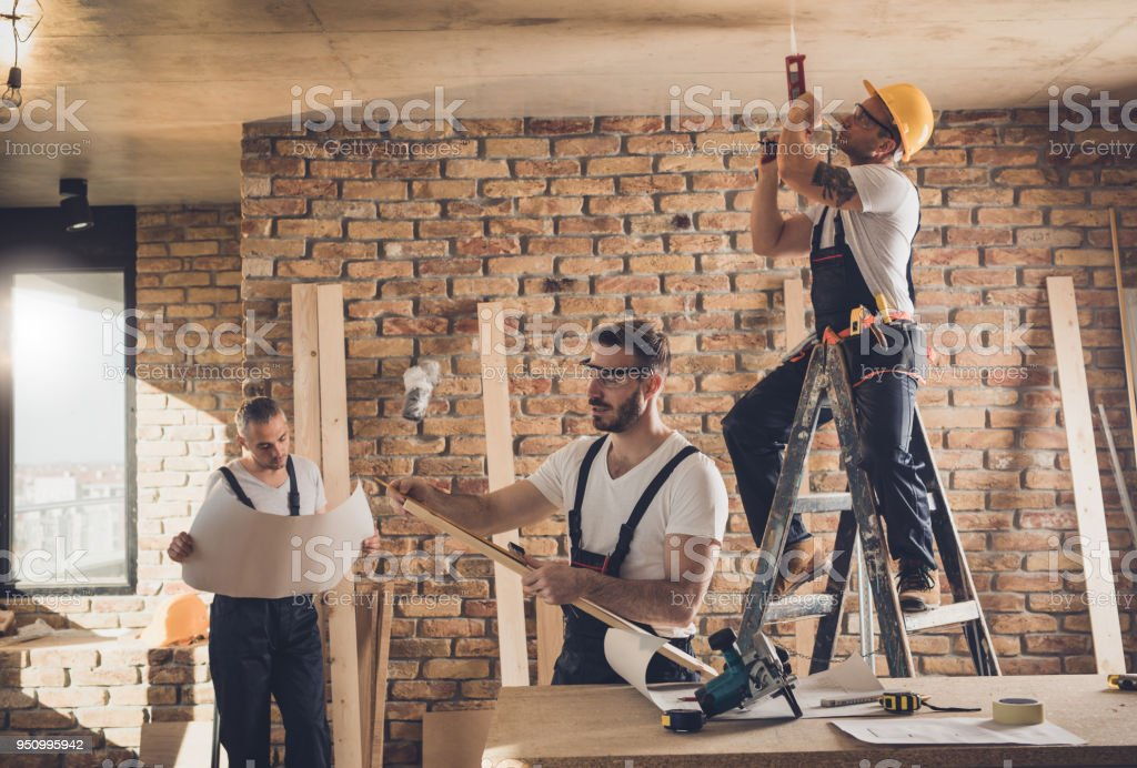 Group of mid adult construction workers working on home addition inside of a house. stock photo