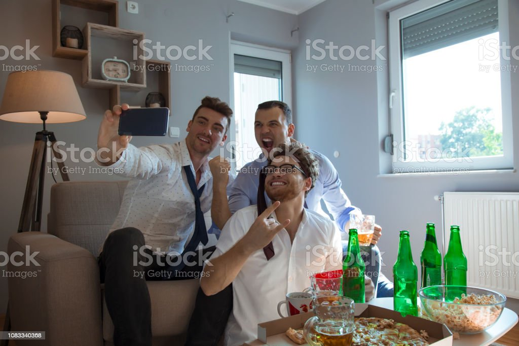 Group of mid adult males watching game after work