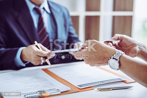 Group of middle age Asian business people and lawyers discussing and sign a contract in meeting room.