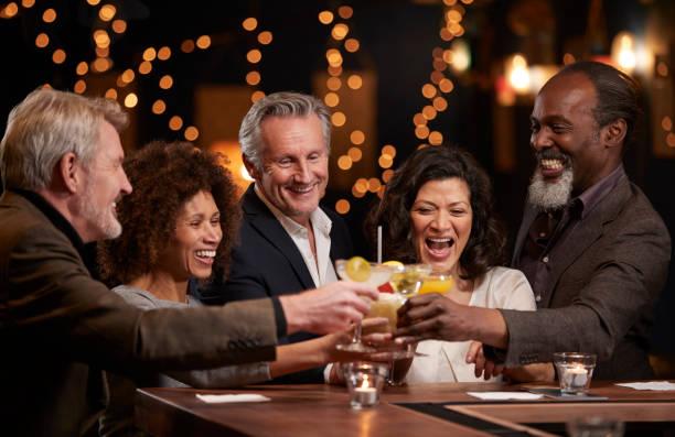 groep van midden leeftijd vrienden vieren in bar samen - happy hour stockfoto's en -beelden