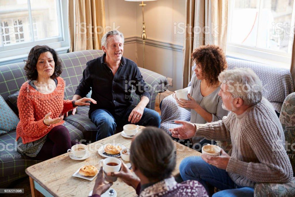 Grupo de la media de edad reunión de amigos alrededor de la mesa en la cafetería - foto de stock